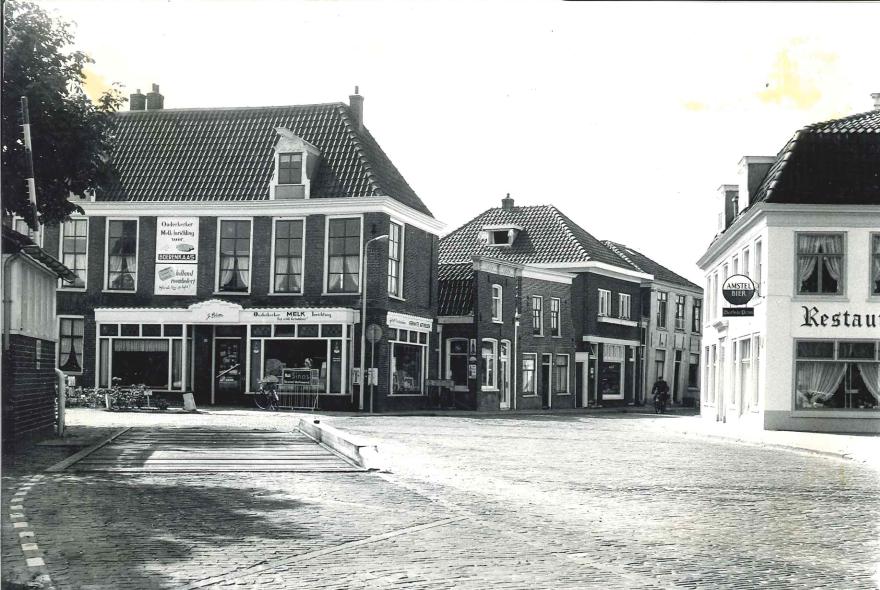 Deze foto is genomen aan de Amstelzijde in augustus 1964. Links de voertuigenweegbrug waarop landbouwwerktuigen met lading werden gewogen en bijbehorend dienstgebouwtje annex urinoir. Daarachter het winkelwoonhuis uit de 19e eeuw, waar in 1964 de Ouderkerker Melkinrichting zat van J. Blom. Rechts restaurant de Oude Prins, waar momenteel restaurant Loetje aan de Amstel in zit. De Amstelzijde met aangrenzende bebouwing is door het Rijk aangewezen als beschermd dorpsgezicht.