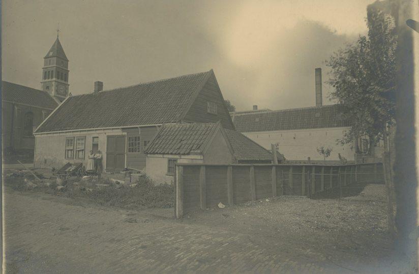 Deze foto is gemaakt op de hoek van het Smedemanplein, met uitzicht op de Dorpskerk. Hoewel de huizen op elkaar lijken, is de huidige woning gebouwd in 1976. Ook de Dorpskerk is kort na de foto uit 1924 veranderd: in 1925 is de kerk uitgebreid met zijbeuken (links zichtbaar op de foto van nu). In 1927 werd de toren beschadigd door blikseminslag en in 1928 vervangen door de huidige toren.